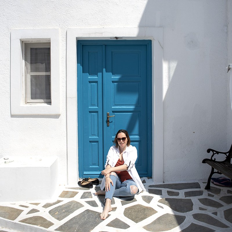Amy Weir founder of Pick and Mix Digital sitting in front of a blue door in greece